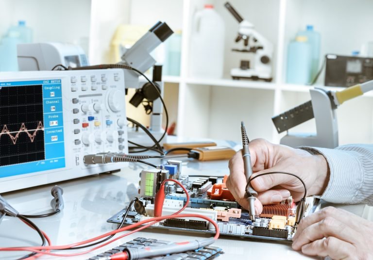 Electronics repair service, hands of senior tech reparing an electronic circuit